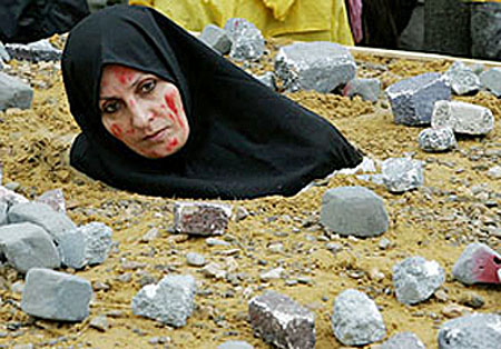 An Iranian woman, dressed up as a victim of death by stoning, takes ...
