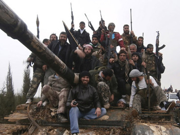 Free Syrian Army fighters pose on a tank, which they say was captured from the Syrian army loyal to President Bashar al-Assad, after clashes in Qasseer