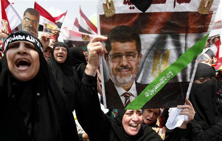 A supporter of deposed Egyptian President Mohamed Mursi holds up a sign with an image of Mursi as they protest at the Rabaa Adawiya square in Cairo