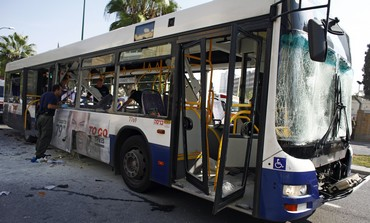 Israeli police officer looks at a damaged bus after an explosion in Tel Aviv