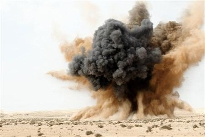 A rebel holds his ears as a bomb launched by a Libyan air force jet loyal to Libya's leader Muammar Gaddafi explodes in the desert near Brega