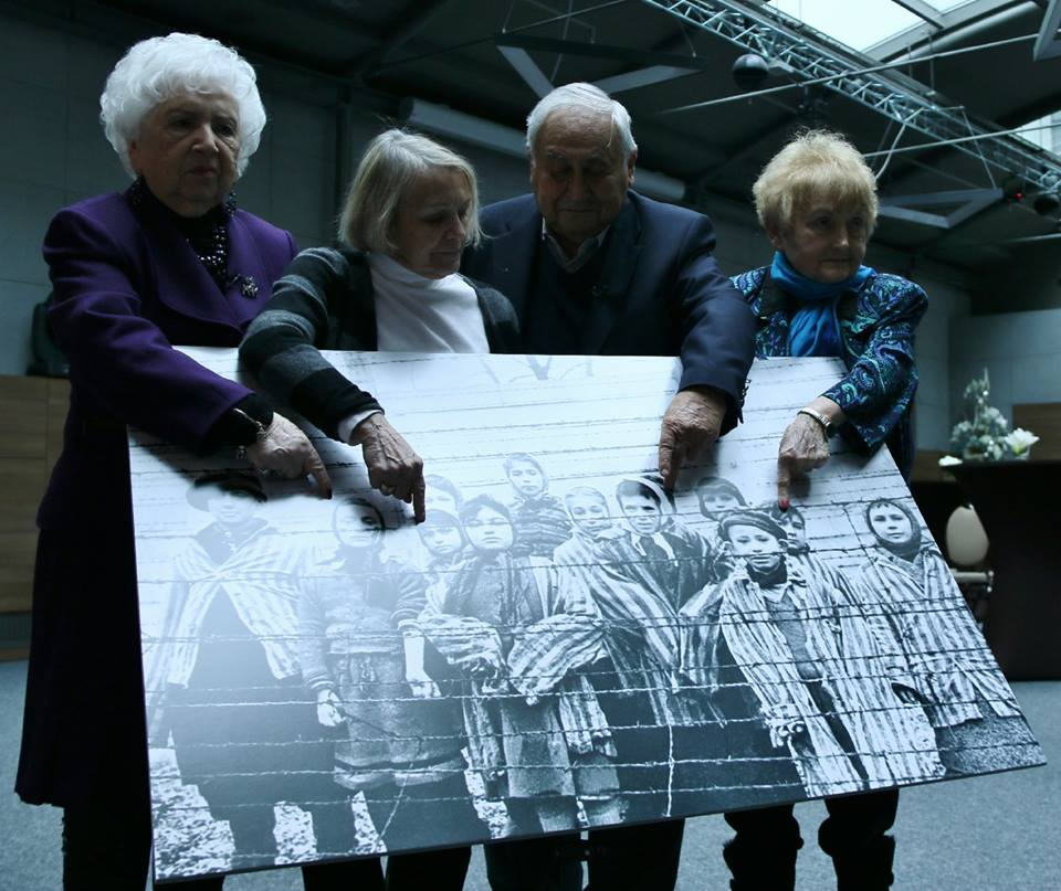 HOLOCAUST SURVIVORS POINT TO PICTURE AS CHILDREN