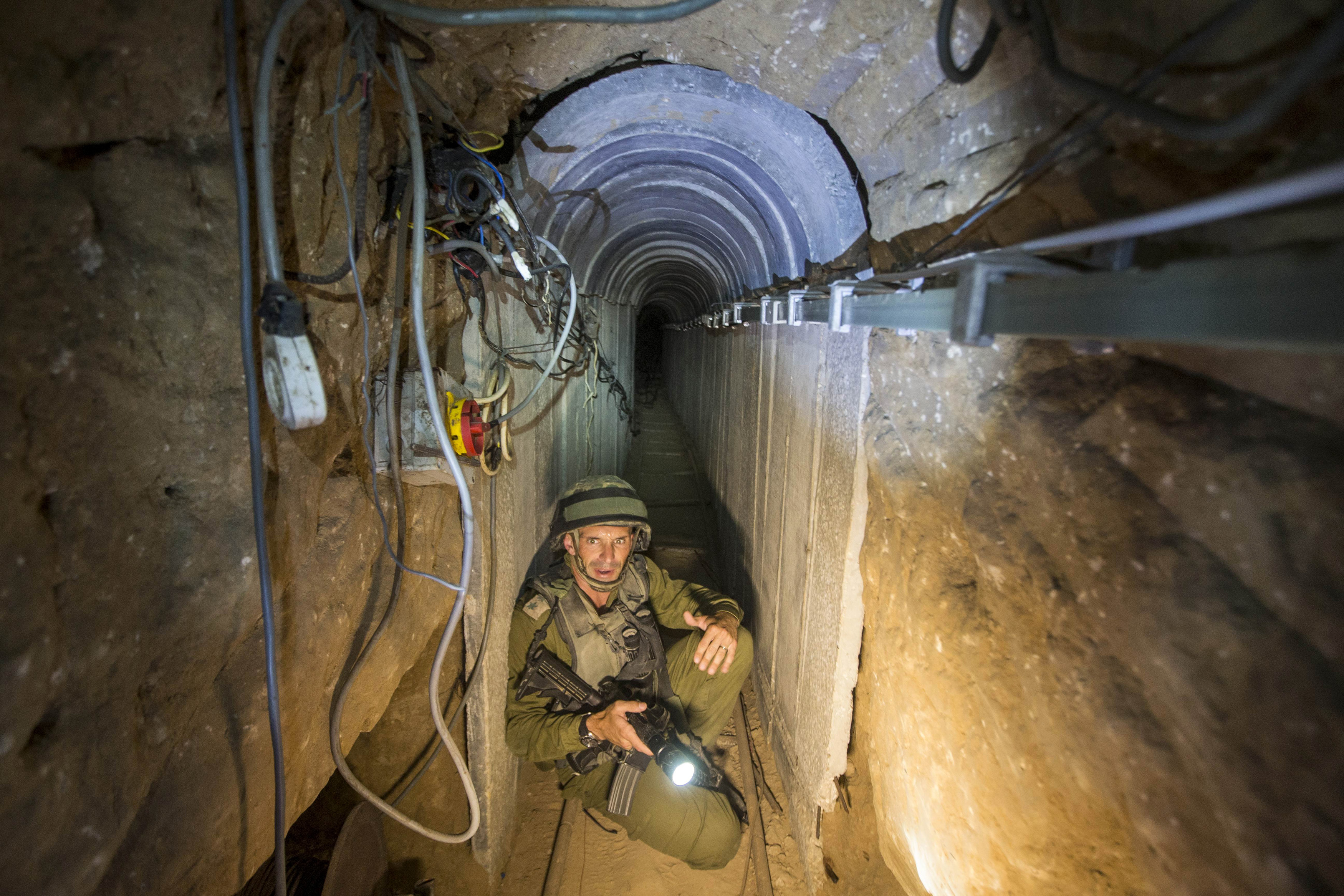An Israeli army officer gives explanations to journalists during an army organised tour in a tunnel said to be used by Palestinian militants for cross-border attacks, July 25, 2014. U.S. Secretary of State John Kerry pressed regional leaders to nail down a Gaza ceasefire on Friday as the civilian death toll soared, and further violence flared between Israelis and Palestinians in the occupied West Bank and Jerusalem. REUTERS/Jack Guez/Pool (CIVIL UNREST MILITARY POLITICS TPX IMAGES OF THE DAY CONFLICT) - RTR40580